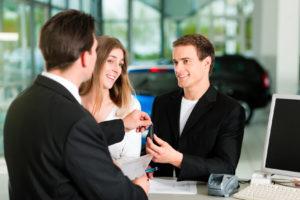 Ein junges Paar nimmt beim Autohändler nach der Vertragsunterschrift den Autoschlüssel entgegen