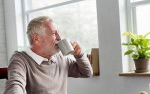 Ein älterer Mann trinkt Kaffee und sieht dabei aus dem Fenster