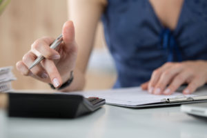 Junge Frau im Business Outfit nutzt einen Taschenrechner und Dokumente