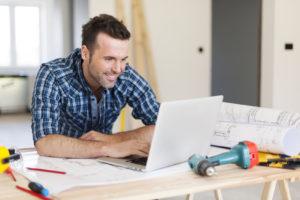 Ein lächelnder Bauherr am schreibtisch mit Werkzeugen und einem Laptop