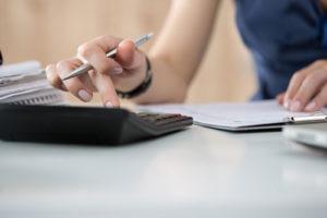 Eine junge Frau rechnet mit einem Taschenrechner und prüft Dokumente