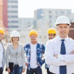 Bauleiter im Vordergrund mit Bauarbeitern im Hintergrund