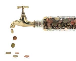Aus einem Wasserhahn tropfen Geldmünzen