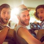 Drei lachende Männer sitzen zusammen im Auto und drehen sich zur Kamera nach hinten um