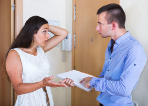 Ein Vermieter deutet auf einen Vertrag, eine Mieterin streitet sich mit ihm darüber