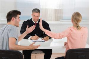 Ein Mann und eine Frau streiten sich vor einem Richter