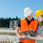 Zwei Bauarbeiter nutzen einen Tablet Computer auf eienr Baustelle