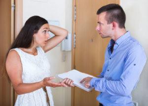 Verzweifelte FRau streitet vor Wohnungstür mit einem Mann, der ein Klemmbrett mit einem Dokument hält