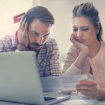 Ein unzufriedenes Paar grübelt über ein Dokument und nutzt einen Laptop
