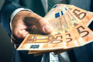 Ein Mann im Anzug streckt mehrere fünfzig Euro Scheine vor