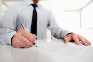 Ein Mann mit Hemd und Krawatte unterzeichnet offizielle Papiere