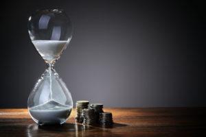 Eine gläserne Sanduhr steht auf einem dunklen Tisch, auf dem auf einige Münzenstapel stehen