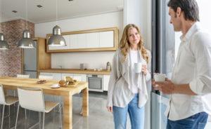Ein Paar steht in einer offenen Küche und trinkt Kaffee