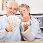 Fröhliches älteres Paar zeigt Geldscheine und ein Modelhaus