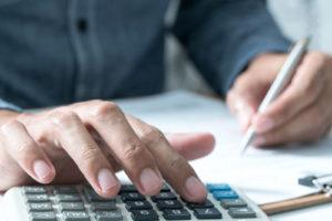 Ein Mann berechnet etwas mit einem Taschenrechner und macht sich Notizen