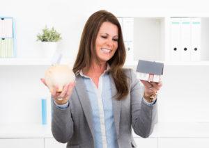 Eine lächelnde Frau hält ein Sparschwin und ein Modellhaus in den Händen