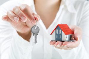 Eine Frau hält vor sich ein kleines Modellhaus und zwei Hausschlüssel