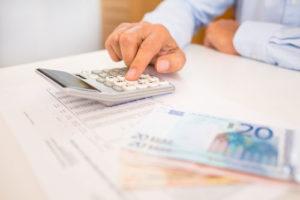 Ein Mann am Schreibtisch nutzt einen Taschenrechner, daneben liegen Euroscheine und eine Seite mit einer Datentabelle