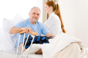 Ein älterer Mann mit Bein im Gips liegt im Krankenhaus und eine Krankenschwester versorgt ihn