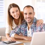 Junges Paar vor Laptop und Taschenrechner
