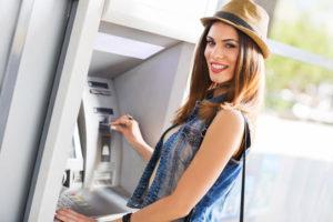 Eine junge lächelnde Frau steht am Geldautomaten