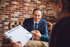 Ein Berater erklärt einer Frau einen Plan anhand eines Kalenders
