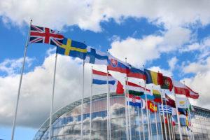 Die Flaggen Europas im Wind vor einem gläsernen Gebäude und blauem Himmel
