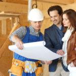Ein Bauarbeiter erklärt den zukünftigen Hausherren den Bauplan