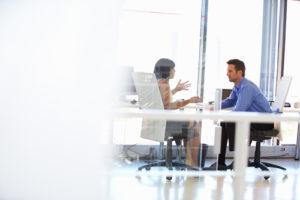 Zwei Personen unterhalten sich in einem Büro