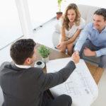 Ein glückliches junges Paar gibt einem Architekten nach der Besprechung de sBauplans die Hand