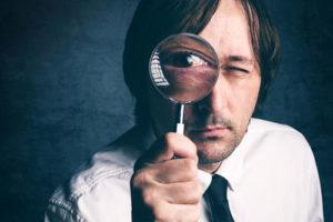 Ein Mann hält sich eine Lupe vor sein Auge