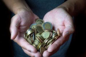Eine Person hält Euromünzgeld in beiden Händen