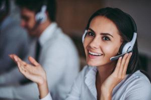 Frau mit Headset führt Telefonat am Arbeitsplatz