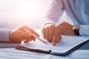 Zwei Personen sitzen an einem Bürotisch über einem papierhaften Dokument
