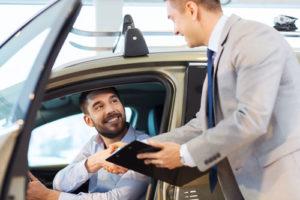 Ein Kunde sitzt im Auto und gibt dem Autohändler die Hand