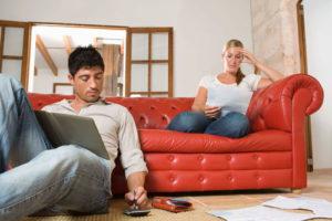 Ein junges Paar sitzt auf einer roten Couch und rechnet Unterlagen nach