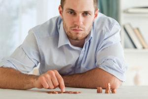Ein nachdenklicher Mann zählt Münzen auf dem Tisch