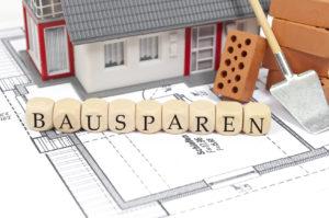 Vor einem Spielzeughaus stehen Buchstabenwürfel, die das Wort Bausparvertrag bilden