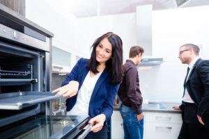 Ein Paar bewundert eine moderne Küche und wird von einem Verkäufer beraten