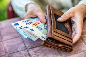 Eine ältere Frau zieht einige Geldscheine aus ihrem Geldbeutel