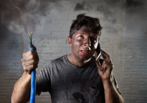 Ein Mann voller Russ hält ein Elekrokabel in der einen Hand und telefoniert mit der anderen