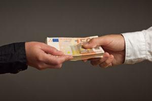 Eine Hand reicht einer anderen ein Bündel Geldscheine