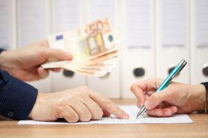 Eine Person händigt Geld aus gegen eine Unterschrift unter ein Dokument