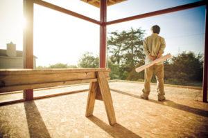 Bauherr mit Bauplan steht nachdenklich in unfertigem Gebäude und blickt in die Ferne
