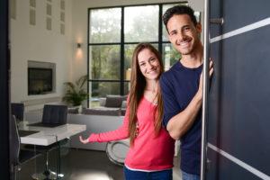 Ein freundliches junges Paar öffnet einlandend die Wohnugnstür