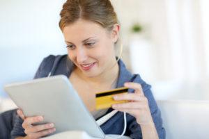 Junge Frau surft mit Tablet und hält eine Kreditkarte in der Hand