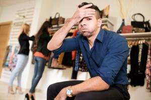 Gestresster Mann greift sich an den Kopf und im Hintergrund suchen zwei Frauen Kleidung aus