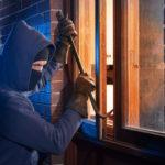 Ein Einbrecher hebelt mit einem Stemmeisen ein Fenster auf