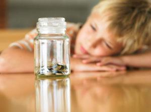 Junge schaut veträumt in ein Glas mit gesammelten Münzen