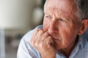 Ein älterer Mann stützt seinen Kopf auf und blickt gedankenverloren in die Ferne